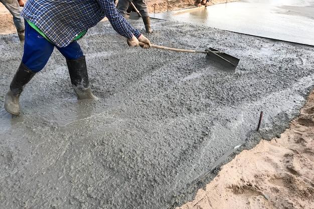 Operai che versano pavimenti in cemento armato in loco
