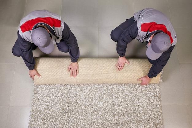 Lavoratori che rotolano tappeto sul pavimento a casa, vista da sopra