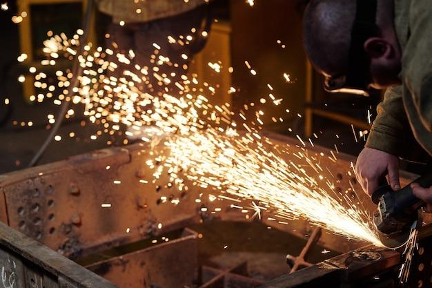 Lavoratori che indossano uniformi industriali e maschera di ferro saldato negli impianti di saldatura dell'acciaio