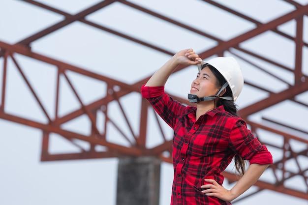 Donna dei lavoratori che tiene un casco in mano alla vigilia delle vacanze, buone feste, festa del lavoro