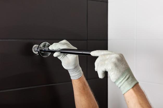 Le mani dei lavoratori installano il tubo del rubinetto della doccia incorporato