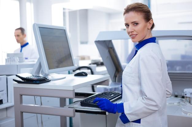 Atmosfera di lavoro. risolvi la simpatica scienziata che sorride mentre si trova in laboratorio e digita