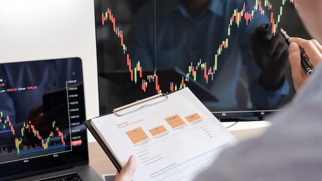 Uomo d'affari, team di broker o commercianti che parlano di forex su più schermi di computer