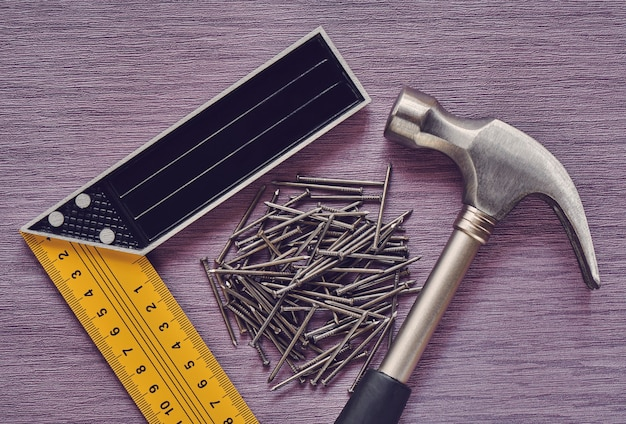 Utensili da falegnameria funzionanti, martello, angolo di marcatura e chiodi