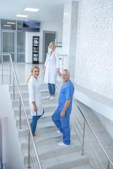 Giorno lavorativo. squadra di operai medici sorridenti che vanno al piano di sopra