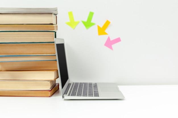 Scrivania aperta. computer portatile aperto, libri e altri articoli per ufficio