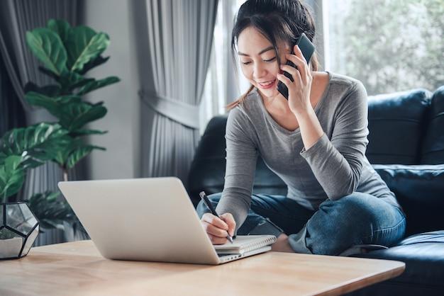 Lavorando da casa, donna che parla sul telefono cellulare e utilizzando il laptop.