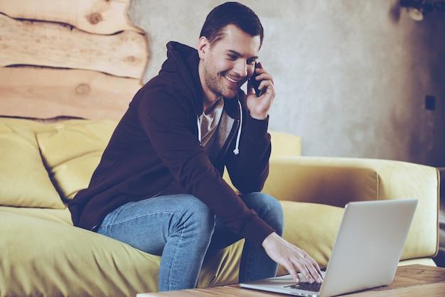 Lavorare da casa con piacere. giovane allegro che usa il suo laptop e parla al cellulare con un sorriso mentre è seduto sul divano di casa