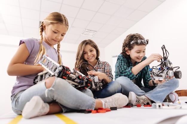 Lavorare in gruppo. affascinanti bambini ispirati e allegri seduti nell'aula di scienze e utilizzano gadget e dispositivi mentre esprimono positività