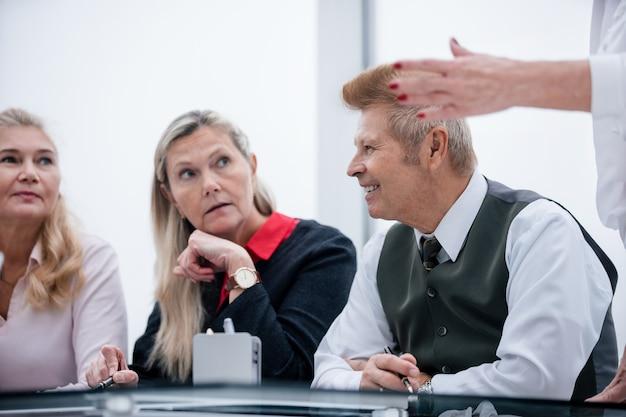 Il gruppo di lavoro discute le attività correnti in una riunione in ufficio. concetto di affari