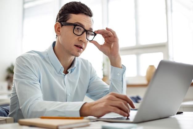 Lavorando. uomo dai capelli scuri concentrato bello che lavora al suo laptop e che tocca gli occhiali mentre era seduto al tavolo