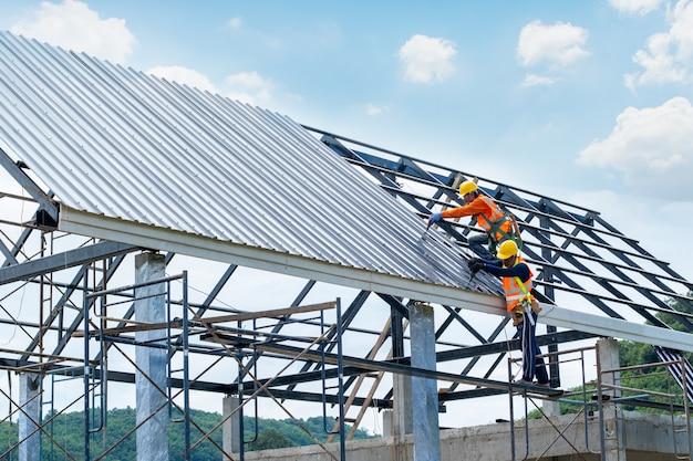 Lavorando su apparecchiature di altezza. il lavoratore di costruzione che indossa l'imbracatura di sicurezza sta lavorando sulla casa sul tetto in cantiere.
