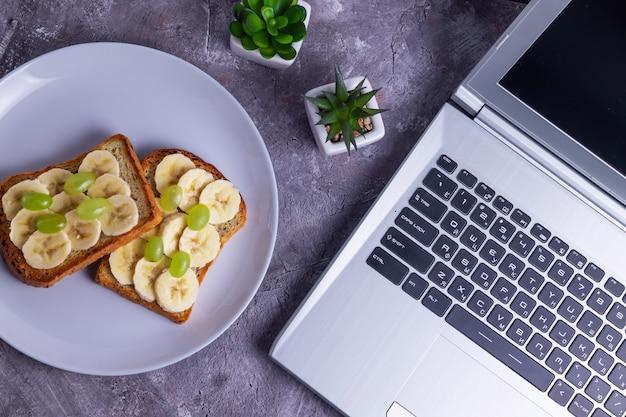 Lavorare su un laptop come libero professionista e un pasto sano brindisi croccanti con banana e uva