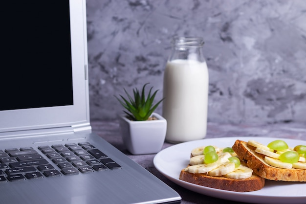 Lavorare su un laptop con freelance e un pasto sano brindisi croccanti con banana