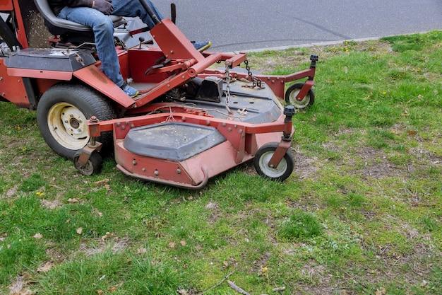 Falciatrice da giardino funzionante su prato verde con erba tagliata nello strumento di lavoro per la cura del giardino