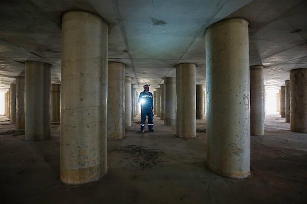 Palo di ispezione maschio funzionante sotterraneo del tunnel dell'attrezzatura del serbatoio utilizzando la torcia all'interno sotto il serbatoio.