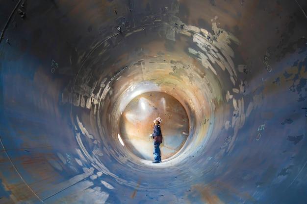 Saldatura di ispezione maschio funzionante nel sottosuolo del tunnel dell'attrezzatura del serbatoio utilizzando la torcia nel lato confinato.