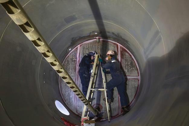 Lavoro maschio due saldatura di ispezione sotterranea del tunnel dell'attrezzatura del serbatoio utilizzando la torcia elettrica nel lato confinato.