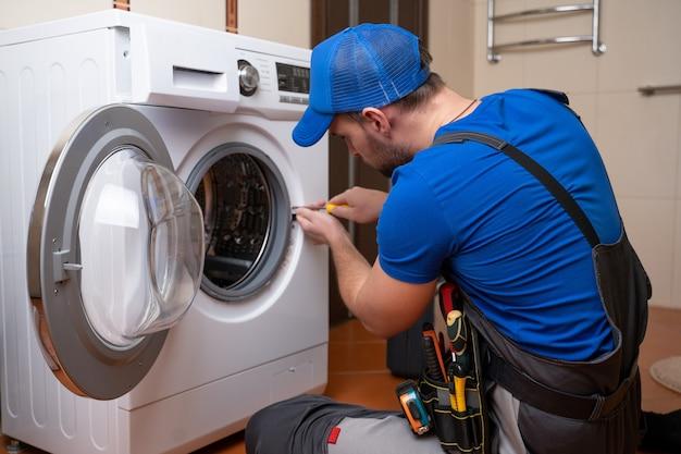 L'idraulico dell'uomo di lavoro ripara una lavatrice nell'installazione domestica della lavatrice o ripara l'idraulico che collega l'apparecchio