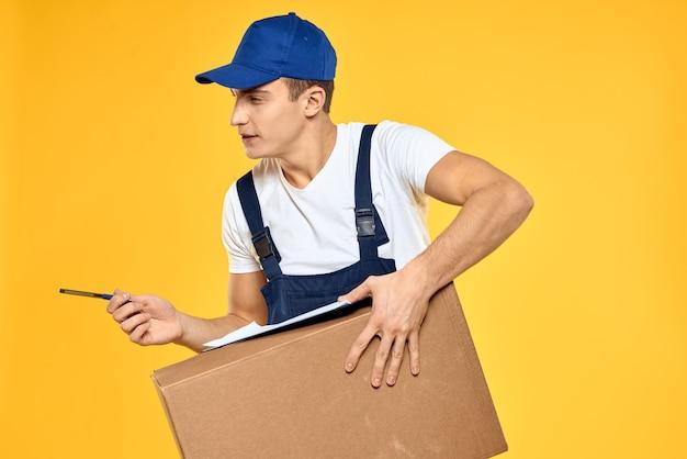 Uomo di lavoro in uniforme con sfondo giallo di servizio di caricamento consegna a mano scatola