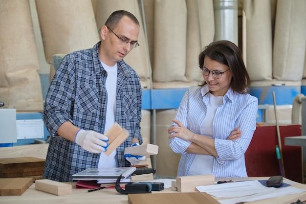 Uomo e donna che lavorano, falegnameria, operai che discutono di produzione di mobili
