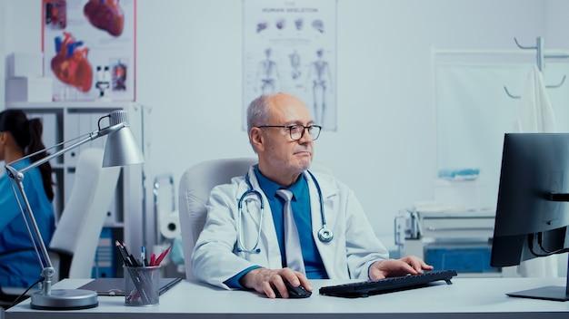 Lavorare in una moderna clinica privata con un'infermiera che controlla i raggi x nella parte posteriore mentre il medico sta digitando al pc davanti. clinica moderna medico del sistema sanitario medico specialista in uniformi speciali