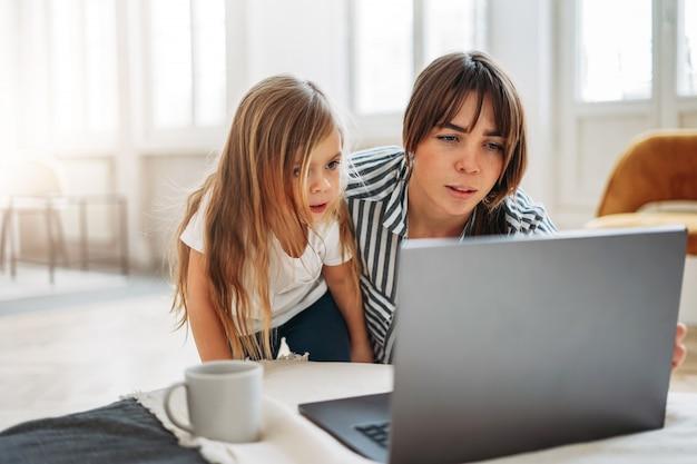 Le free lance lavoratrici della mamma con la piccola figlia guardano insieme al computer portatile nell'interno luminoso a casa