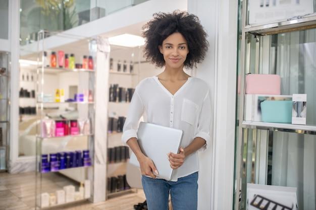 Atmosfera lavorativa. sorridente giovane donna alla moda con il portatile in mano nella bellissima camera con cosmetici