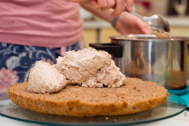 Processo di lavorazione della torta a casa. primo piano di mano femminile topping crema sul biscotto al cioccolato.