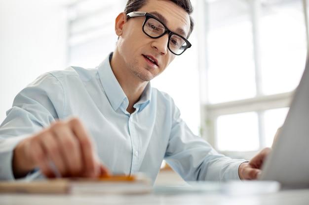 Processo lavorativo. bell'uomo dai capelli scuri serio che lavora al suo computer portatile e pensa mentre si siede al tavolo