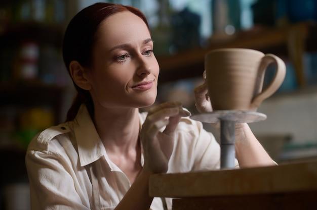 Processo lavorativo. una giovane donna che lavora in un laboratorio di ceramica e sembra coinvolta