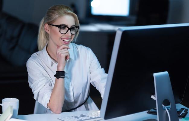 Lavorando al progetto. coinvolto membro del personale qualificato e carismatico seduto in ufficio e utilizzando dispositivi moderni mentre lavora al progetto