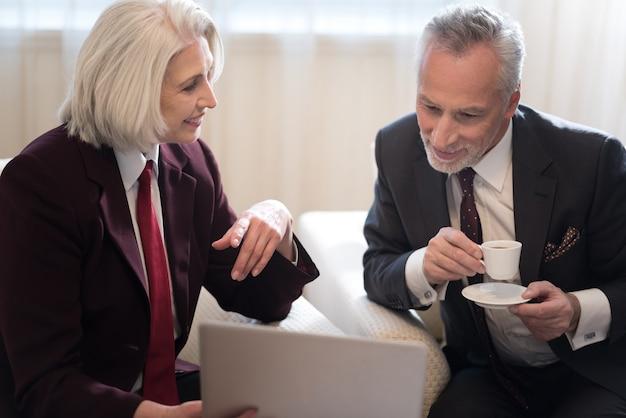Lavorando insieme al progetto. allegro sorridente imprenditrice invecchiato guardando il suo collega e seduto in ufficio mentre si tiene il laptop