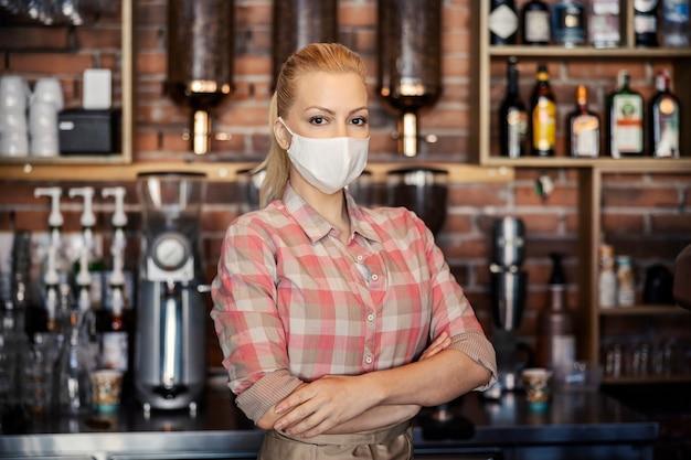 Lavorare in un ristorante e pandemia di coronavirus. inquadratura ravvicinata di una donna che sta dietro un bar del ristorante e indossa una camicia a quadri color pastello e una maschera protettiva la cameriera ha incrociato le braccia con un sorriso