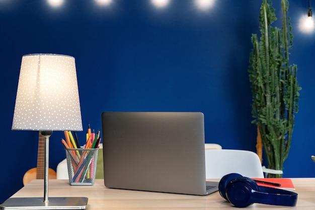 Tavolo di lavoro con il computer portatile contro la parete blu in appartamento moderno