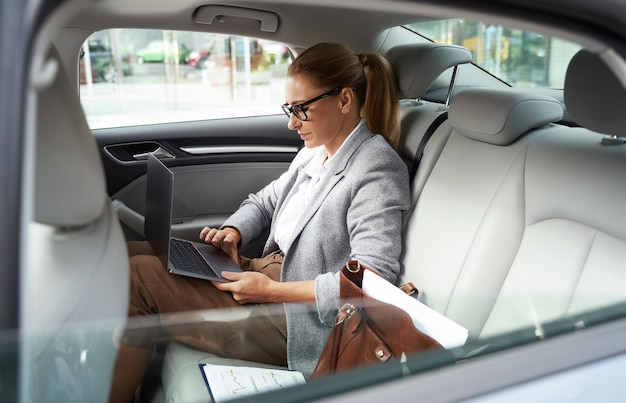 Lavorare in taxi vista laterale di una donna d'affari di successo che indossa occhiali usando il laptop mentre