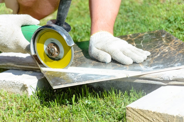 Il piastrellista di lavoro taglia la piastrella con una smerigliatrice angolare sul pavimento, movimento nel telaio, lavoro sporco e polveroso