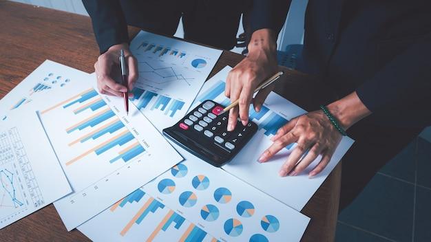 Lavorare insieme donne d'affari con grafici finanziari e grafico con calcolatrice per il calcolo dei dati e la gestione.