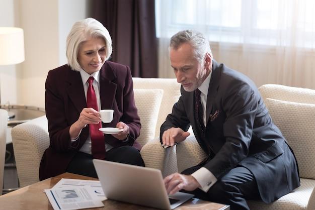 Lavorare insieme. piacevole uomo d'affari invecchiato barbuto guardando e indicando il laptop e seduto in hotel mentre si lavora al progetto con il suo collega ed esprime interesse