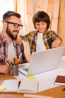 Lavorare insieme al padre. felice giovane uomo che lavora al computer portatile mentre il suo piccolo figlio lo indica