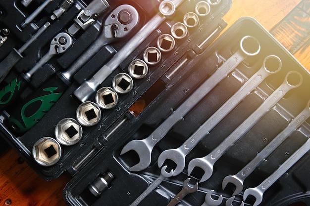 Gli strumenti di lavoro hanno messo le chiavi dei meccanici dell'automobile in scatola nera. vista dall'alto e riflesso lente.