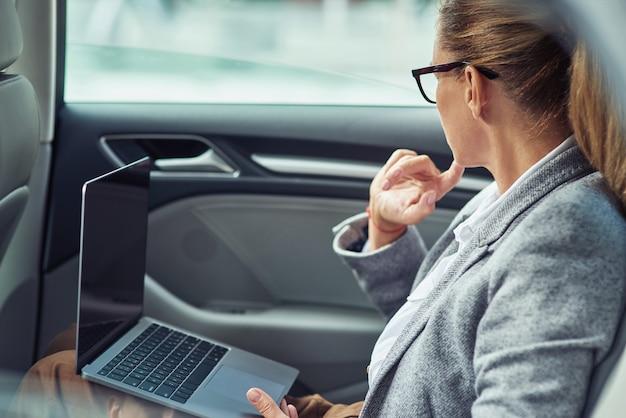 Lavorando sulla strada per la vista laterale dell'ufficio di una donna d'affari caucasica che lavora su