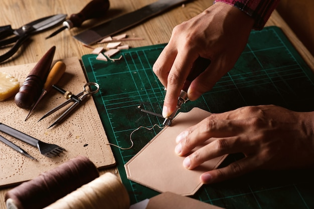 Lavorazione con pelle conciata al vegetale. la pelle e gli strumenti del mestiere.