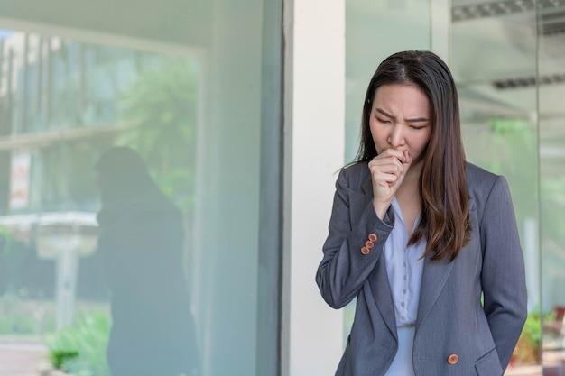 Concetto di donna lavoratrice una donna lavoratrice che tossisce dopo aver contattato molte persone mentre lavorava senza alcuna protezione.