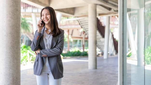 Concetto di donna lavoratrice una donna lavoratrice con faccina sorridente che parla al telefono con il suo socio in affari.