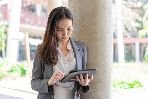 Concetto di donna che lavora una giovane donna d'affari che lavora online per la sua attività con i dispositivi con maniglia, tablet, al di fuori del posto di lavoro.