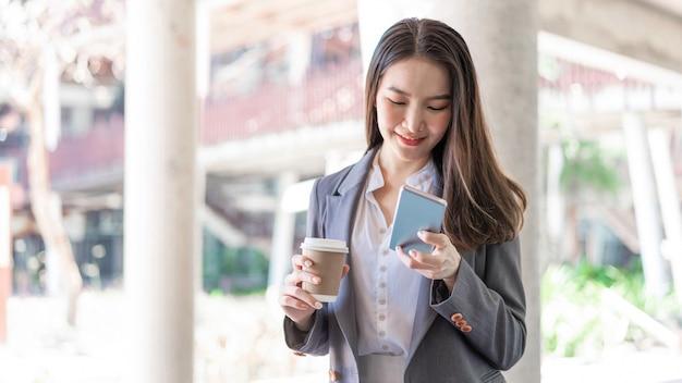 Concetto di donna lavoratrice una giovane manager femminile che partecipa alla videoconferenza e tiene in mano una tazza di caffè.