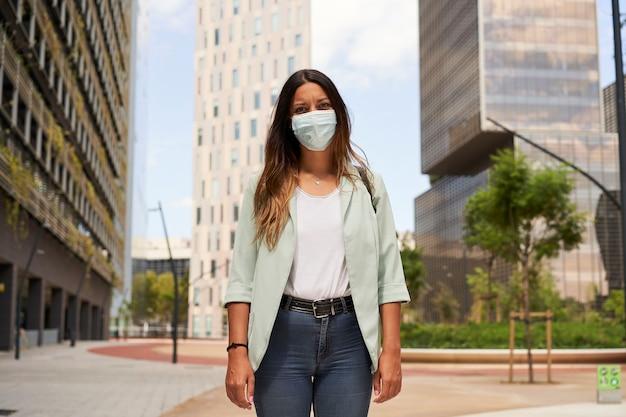 Donna lavoratrice in un centro finanziario con indosso una maschera per la pandemia di coronavirus.