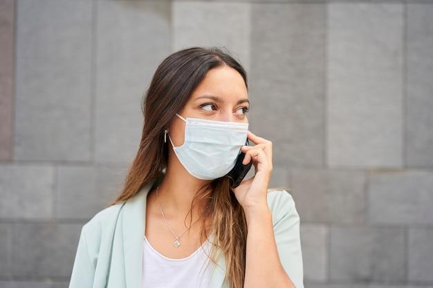 Donna che lavora parlando al telefono. si traveste da pandemia di coronavirus.