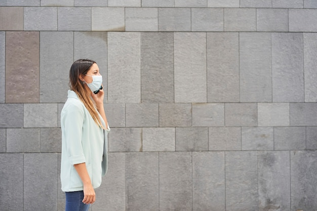 Donna lavoratrice con maschera facciale parlando al telefono.